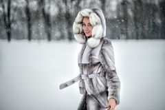 Lycklig kvinna som har gyckel på den insnöade vinterskogen Royaltyfri Foto