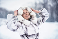 Lycklig kvinna som har gyckel på den insnöade vinterskogen Royaltyfria Foton
