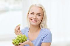 Lycklig kvinna som hemma äter druvor arkivfoto