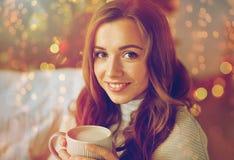 Lycklig kvinna som hemma dricker kakao för jul Arkivfoton