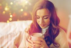 Lycklig kvinna som hemma dricker kakao för jul Fotografering för Bildbyråer