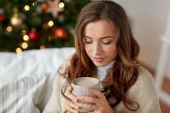 Lycklig kvinna som hemma dricker kakao för jul Royaltyfria Foton