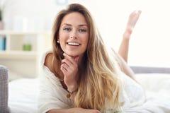 Lycklig kvinna som hemma kopplar av Arkivfoton