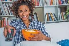 Lycklig kvinna som hemma sitter med hållande ögonen på tv för fjärrkontroll royaltyfri fotografi