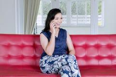 Lycklig kvinna som hemma talar på en telefon fotografering för bildbyråer