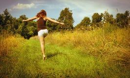 Lycklig kvinna som hoppar over bort i en sätta in royaltyfri bild
