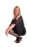 Lycklig kvinna som huka sig ned på golv Arkivfoto
