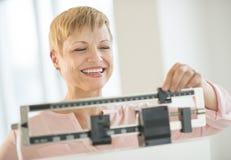 Lycklig kvinna som justerar skalan för jämviktsvikt Royaltyfri Bild