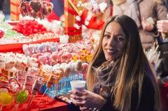 Lycklig kvinna som känner den stads- julviben på natten Lycklig kvinna som ser upp med julljus på natten Arkivfoto