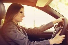 Lycklig kvinna som kör en bil fotografering för bildbyråer