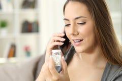 Lycklig kvinna som kallar doktorn som frågar om flaskan av preventivpillerar Royaltyfri Fotografi