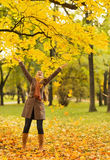 Lycklig kvinna som kastar fallna leaves Arkivfoto