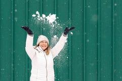 Lycklig kvinna som kastar snö in i luften royaltyfri bild