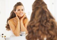 Lycklig kvinna som kontrollerar ansikts- hudvillkor i badrum arkivbild