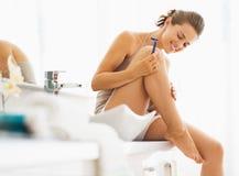 Lycklig kvinna som kontrollerar ben, når att ha rakat Royaltyfri Foto