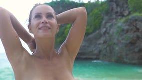 Lycklig kvinna som kopplar av i blått havs- och klippalandskap Härlig kvinna i bikini på sommarhavsstranden tropisk semester stock video
