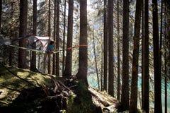 Lycklig kvinna som kopplar av i det hängande tältet som campar i sjöskogträn under solig dag Grupp av vänfolksommar Royaltyfria Foton