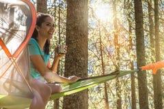 Lycklig kvinna som kopplar av i det hängande tältet som campar i skogträn under solig dag Grupp av affärsföretaget för vänfolksom Royaltyfri Bild