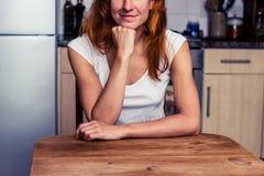 Lycklig kvinna som kopplar av i hennes kök arkivfoton