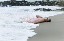 Lycklig kvinna som ligger i vågor på stranden med att plaska för vatten Arkivbild