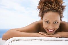 Lycklig kvinna som ligger på massagetabellen royaltyfri foto