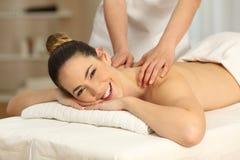 Lycklig kvinna som mottar en massage i en brunnsort som ser dig arkivbild