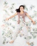 Lycklig kvinna som mycket sover i en säng av pengar fotografering för bildbyråer