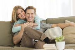 Lycklig kvinna som omfamnar mannen på Sofa At Home royaltyfri foto