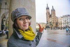 Lycklig kvinna som pekar till marknadsfyrkanten av Krakow, Polen Royaltyfria Foton