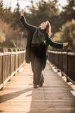 Lycklig kvinna som poserar på en trägammal bro i skogen, Enjoyin Arkivbild
