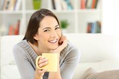 Lycklig kvinna som poserar rymma en kaffekopp Arkivbilder