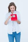 Lycklig kvinna som öppnar en gåva Arkivfoto