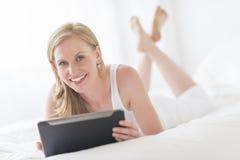 Lycklig kvinna som rymmer den Digital minnestavlan, medan ligga på säng Royaltyfri Foto
