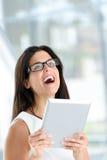 Lycklig kvinna som rymmer den digitala minnestavlan Royaltyfri Foto