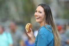 Lycklig kvinna som rymmer en hamburgare som ser dig Arkivfoto
