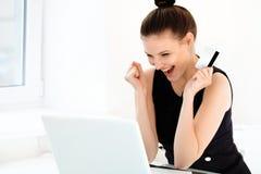 Lycklig kvinna som rymmer en kreditkort och shoppar från internet Royaltyfria Bilder