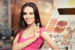Lycklig kvinna som rymmer en sminkborste Fotografering för Bildbyråer