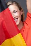 Lycklig kvinna som rymmer en tysk flagga Royaltyfri Bild