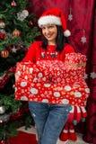 Lycklig kvinna som rymmer många julgåvor royaltyfri foto