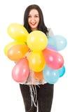 Lycklig kvinna som rymmer många ballonger Royaltyfri Fotografi