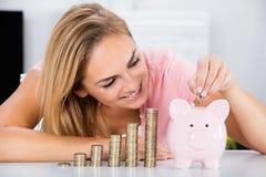 Lycklig kvinna som sätter in myntet i Piggybanken arkivfoton