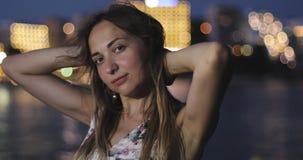 Lycklig kvinna som ser in i kameran och ler i bakgrunden av natthavet lager videofilmer