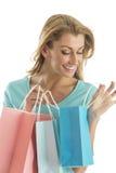 Lycklig kvinna som ser in i shoppingpåse Arkivbild