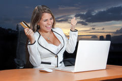 Lycklig kvinna som shoppar direktanslutet genom att använda hennes kreditkort på rengöringsduken Royaltyfria Foton