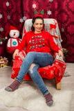 Lycklig kvinna som sitter på stol med julgranen royaltyfri bild