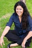 Lycklig kvinna som sitts på gräs Arkivbilder