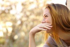 Lycklig kvinna som skrattar täcka hennes mun Arkivfoto