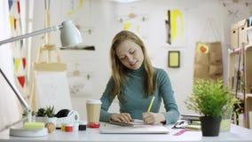Lycklig kvinna som skrivar ett brev vid tabellen stock video