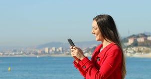 Lycklig kvinna som smsar på telefonen på stranden i vinter