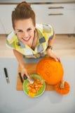 Lycklig kvinna som snider en stor orange pumpaStålar-NOLLA-lykta Arkivbild